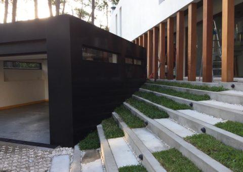 Garage forrado con alucobond negro, con aberturas línea Summa y Gala, en color anolock marrón, Zona Barrio privado Laguna Blanca Manantiales