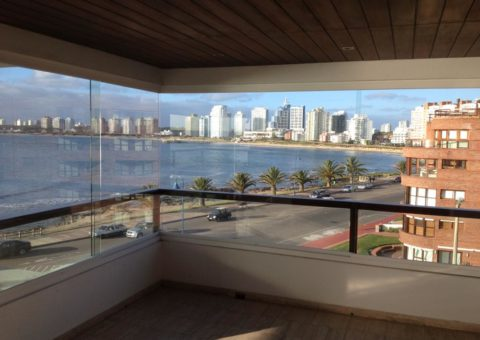 Cerramiento de balcón realizado en cristal incoloro de 10 mm, con sistema corredizo sobre guía de aluminio, zona Península Punta del Este